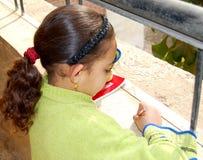 En flicka som studerar och skriver läxa i arabiska Arkivbild