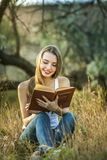 En flicka som utanför läser en bok Arkivfoton