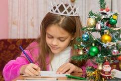 En flicka som väntar på ett nytt år, skrivar brevet till lust royaltyfria foton