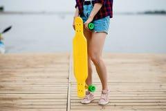 En flicka sombär grov bomullstvill kortslutningar, står på pir och rymmer en gul longboard framme av henne Floden är i arkivfoton