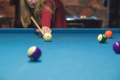 En flicka spelar en billiard på klubban fotografering för bildbyråer