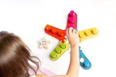 En flicka spelar en lek med kulöra träkvarter sorterare Utvecklingen av formatet, färg royaltyfri fotografi