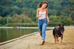 En flicka spelar med hennes hund på stranden i sommar parkerar Fotografering för Bildbyråer