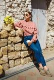En flicka står nära den stads- väggen med en kopp kaffe royaltyfria foton