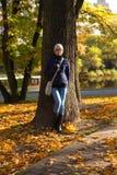 En flicka står nära ett träd royaltyfri foto