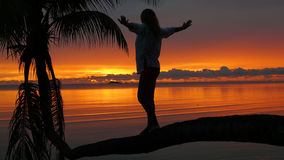 En flicka står på en palmträd på en bakgrund av den röda solnedgången på kusten Arkivfoto