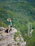 En flicka står på en klippa mot bakgrunden av den gröna skogen royaltyfria foton