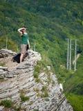 En flicka står på en klippa mot bakgrunden av den gröna skogen royaltyfri bild