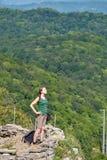 En flicka står på en klippa mot bakgrunden av den gröna skogen arkivfoton