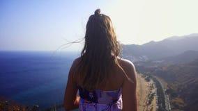 En flicka står på kusten av det blåa havet arkivfilmer
