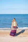 En flicka står tillbaka och ser havet Hippieflickan ser havet Kvinnan med en flaska av vin är vid havet hippie Arkivbild