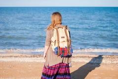En flicka står tillbaka och ser havet Hippieflickan ser havet Kvinnan med en flaska av vin är vid havet hippie Arkivfoto