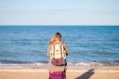 En flicka står tillbaka och ser havet Hippieflickan ser havet Kvinnan med en flaska av vin är vid havet hippie Royaltyfri Bild
