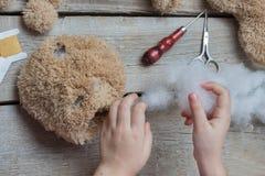 En flicka syr en björnleksak Hemslöjd med barn Barnet fyller leka med en sintepon Arkivfoton