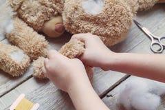 En flicka syr en björnleksak Hemslöjd med barn Barnet fyller leka med en sintepon Royaltyfri Fotografi