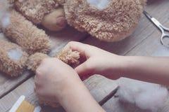 En flicka syr en björnleksak Hemslöjd med barn Barnet fyller leka med en sintepon toning Arkivfoton