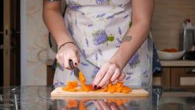 En flicka tärnar kokta morötter arkivfilmer