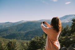 En flicka tar en bild av bergen och skogarna runt om henne på en solig dag fotografering för bildbyråer