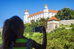 En flicka tar bilder av en vit slott i Bratislava Slott Bratislava Vit slott i Bratislava arkivfoton