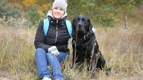 En flicka tar bilder med hennes hund som ser kameran foto fotografering för bildbyråer