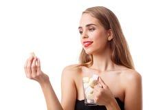 En flicka undersöker en marshmallow i hennes hand på en vit bakgrund arkivbild