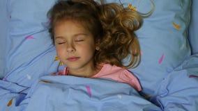 En flicka vaknar upp ömt att le att ligga ner i säng med blå linne stock video