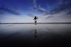 En flickabanhoppning på stranden Arkivfoto