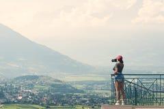 En flickafotograf i ett rött lock med en kamera står på balkongoppositen av italienska berg och byn i södra Tirol elsassisk Arkivfoto