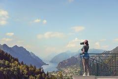 En flickafotograf i ett rött lock med en kamera står på balkongoppositen av italienska berg och byn i södra Tirol elsassisk Arkivbilder