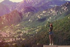 En flickafotograf i ett rött lock med en kamera står på balkongoppositen av italienska berg och byn i södra Tirol elsassisk Fotografering för Bildbyråer