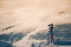 En flickafotograf i ett rött lock med en kamera står på balkongoppositen av italienska berg och moln i södra Tirol Royaltyfri Foto