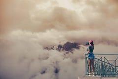 En flickafotograf i ett rött lock med en kamera står på balkongoppositen av italienska berg och moln i södra Tirol Arkivbilder