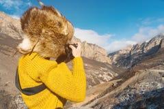 En flickafotograf i en pälshatt och en gul tröja i bergen tar bilder på hennes digitala kamera Fotografering för Bildbyråer