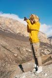 En flickafotograf i en pälshatt och en gul tröja i bergen tar bilder på hennes digitala kamera Royaltyfria Bilder