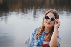 En flickahippy på flodbanken som poserar och ler Royaltyfria Bilder