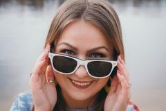 En flickahippy på flodbanken som poserar och ler Arkivfoto