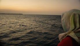 En flickamoslem med skyler stående framme av det utländska stora havet royaltyfria foton