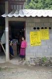 En flickaställning bredvid en dörr i en Thailand by Royaltyfria Bilder