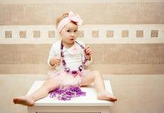 En flickauppklädd som en docka sitter på en byrå royaltyfri foto
