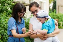 En flickvän för moder` s visar behandla som ett barn en mobiltelefon arkivbild