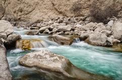 En flod av sötvatten bland vaggar Snabbt flöde för ny aqua i stenarna En skogflod med rent kallt vatten nytt Royaltyfri Fotografi