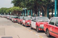 En flotta av Hong Kong åker taxi att vänta på en taxiställning Hong Kong taxi är lätt igenkännliga vid deras röda och vitfärger G arkivbilder