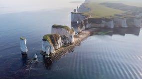 En flyg- sikt av den gamla Harry Rocks längs den Jurassic kusten med kristallklart vatten och vita klippor under en disig himmel arkivbild