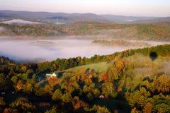 En flyg- sikt av en ballong för varm luft som svävar över den Vermont landssidan Arkivfoto