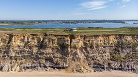 En flyg- sikt av ett coastguardtorn på överkanten av en kulle med den eroderade klippan längs en sandig strand med en hamn i bakg royaltyfria bilder