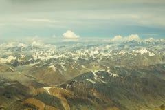 En flyg- sikt av Himalayan ökenberg med snöig maxima under vita moln och blå himmel arkivfoto