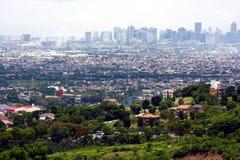En flyg- sikt av kommersiella och bostads- byggnader och etableringar i städerna av Cainta, Taytay, Pasig, Makati och Taguig Fotografering för Bildbyråer