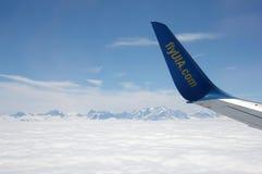 En flygplanvinge över moln Arkivfoto