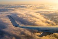 En flygplanvinge som packar ihop över fluffiga moln som solen, börjar till Royaltyfri Bild
