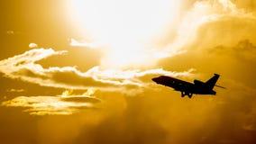 En flygtrafikflygplan i aftonhimlen - ett konturfotografi i panelljuset arkivfoton
